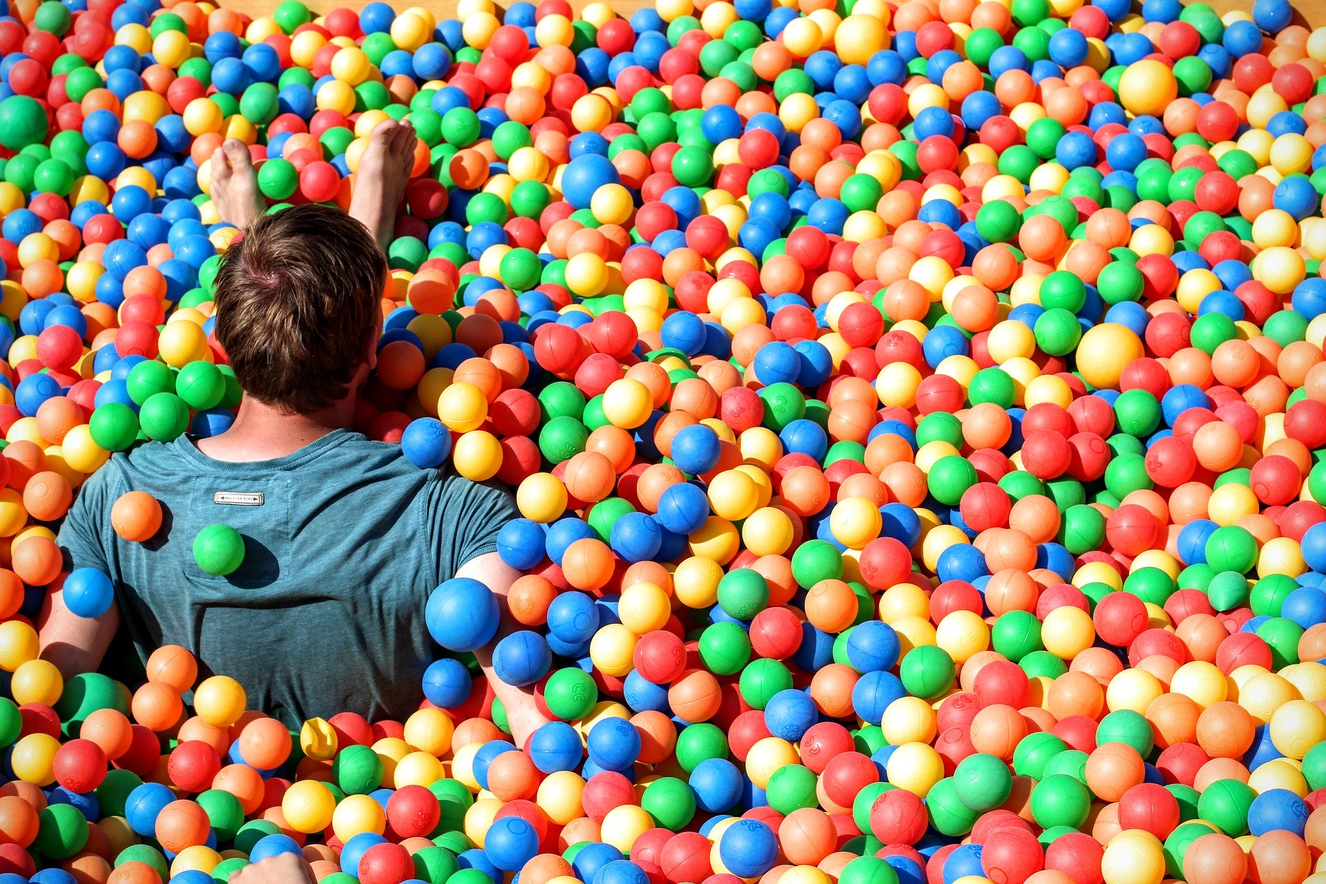 man has fun in a ball pit