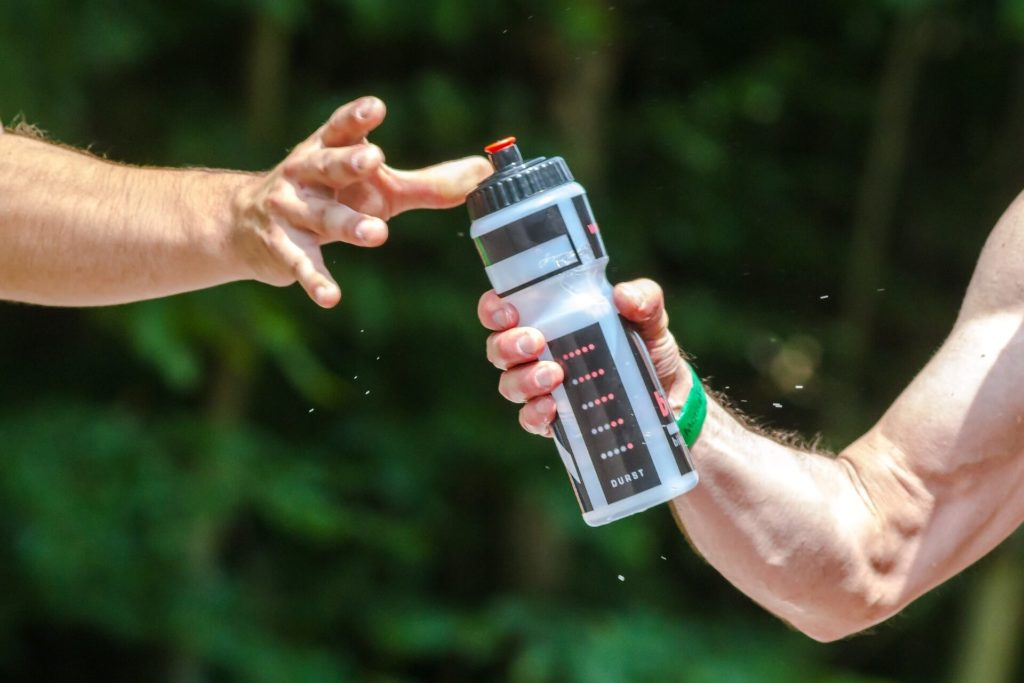 man reaching for water bottle after exercise