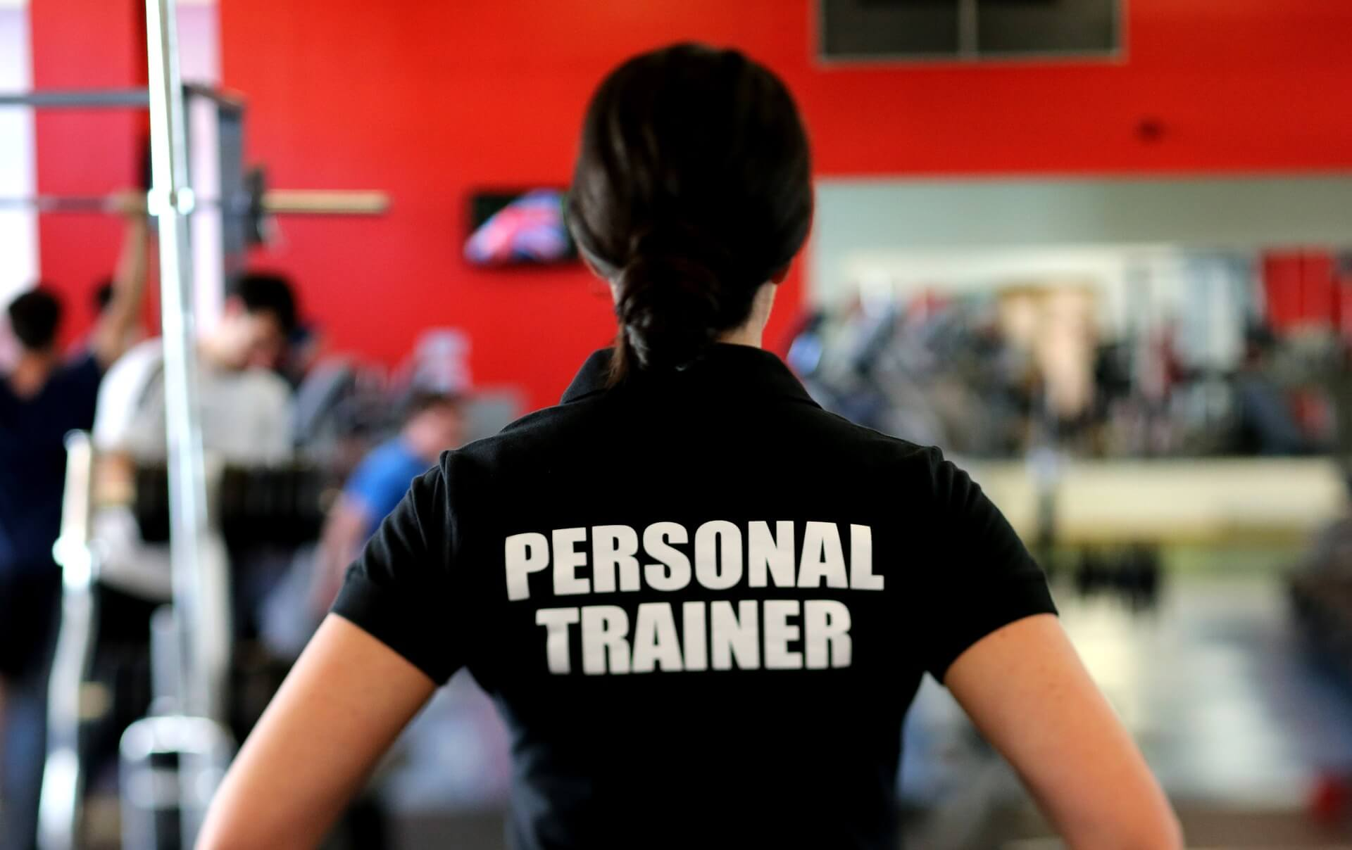 woman in gym wearing personal trainer shirt