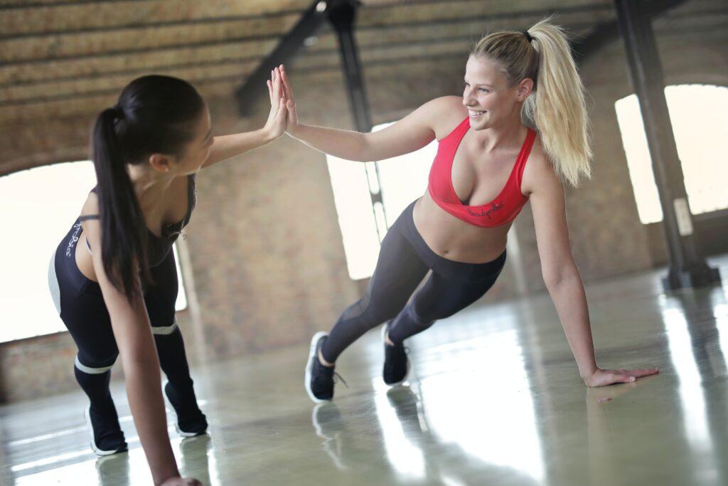 two smiling women doing yoga pose
