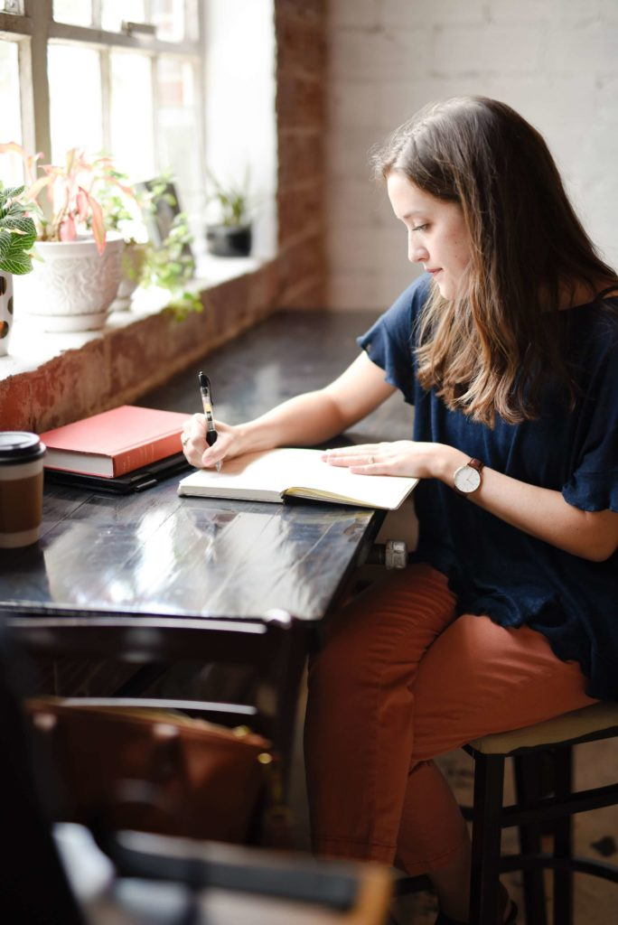 Woman sitting at desk writing in a journal